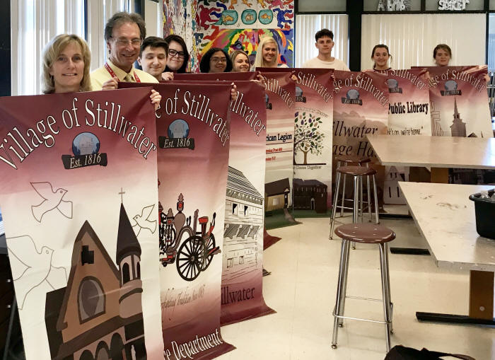 Stillwater art students pose with the banners they made for the village