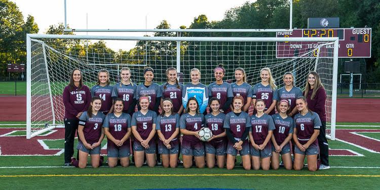 Girls varsity soccer team posing for a photo in front of a soccer goal