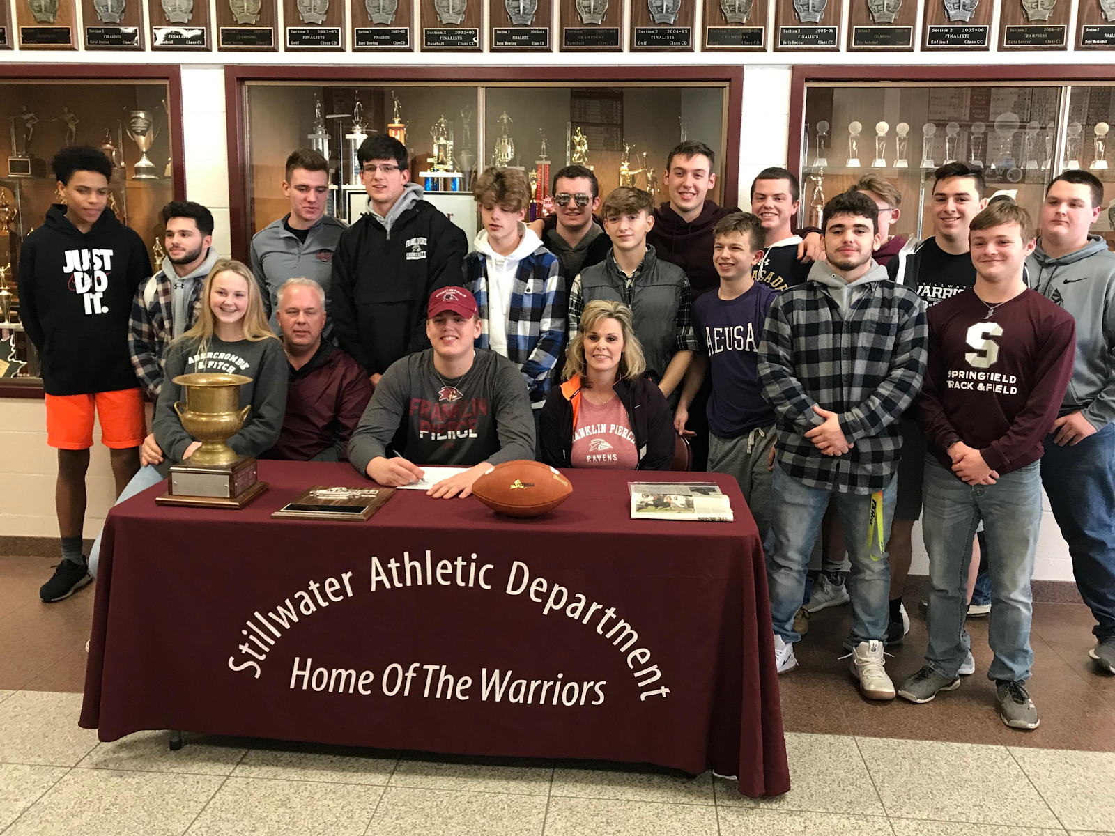 Students and family gathered with athlete at a table