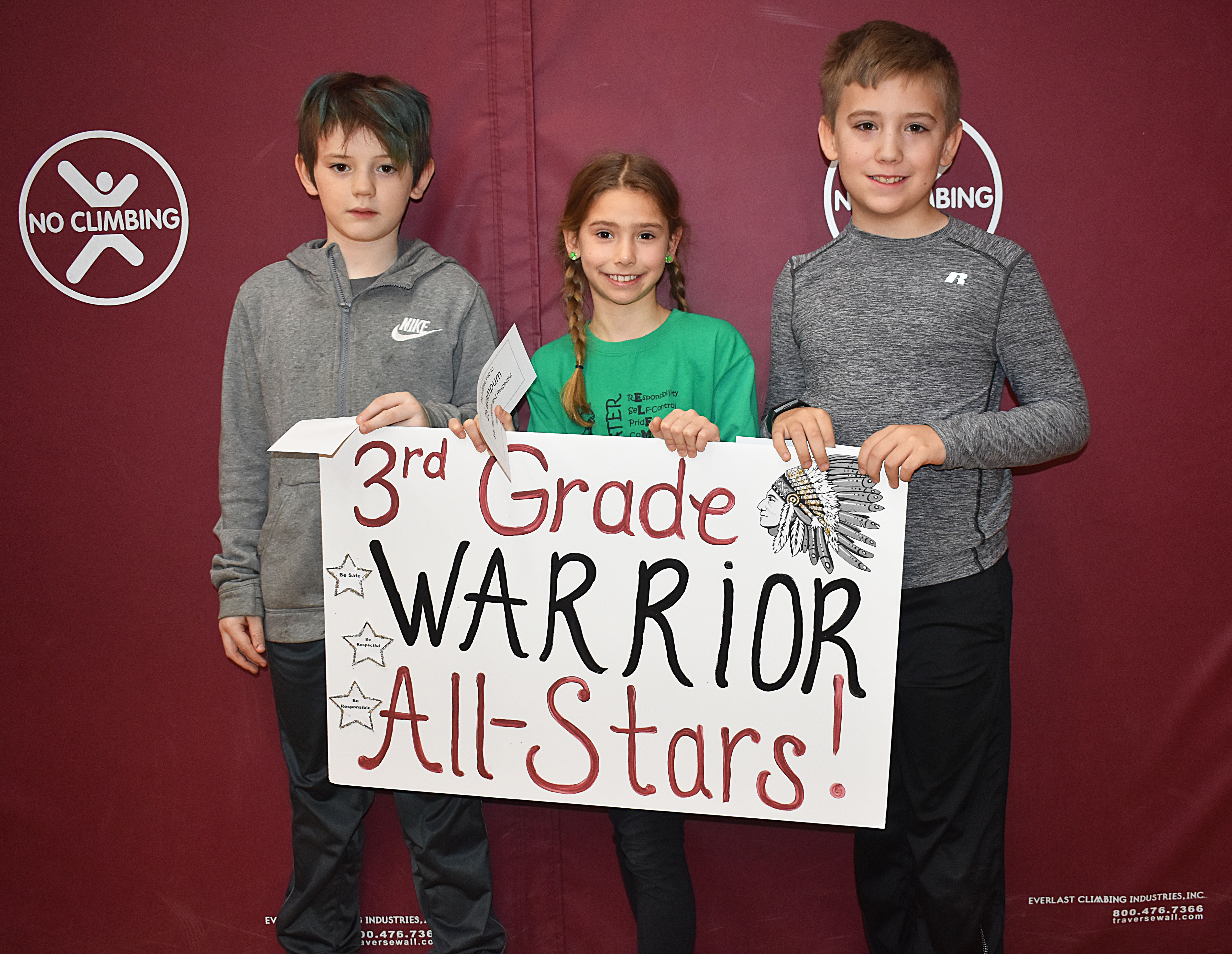 Three third graders gathered together with the third grade sign
