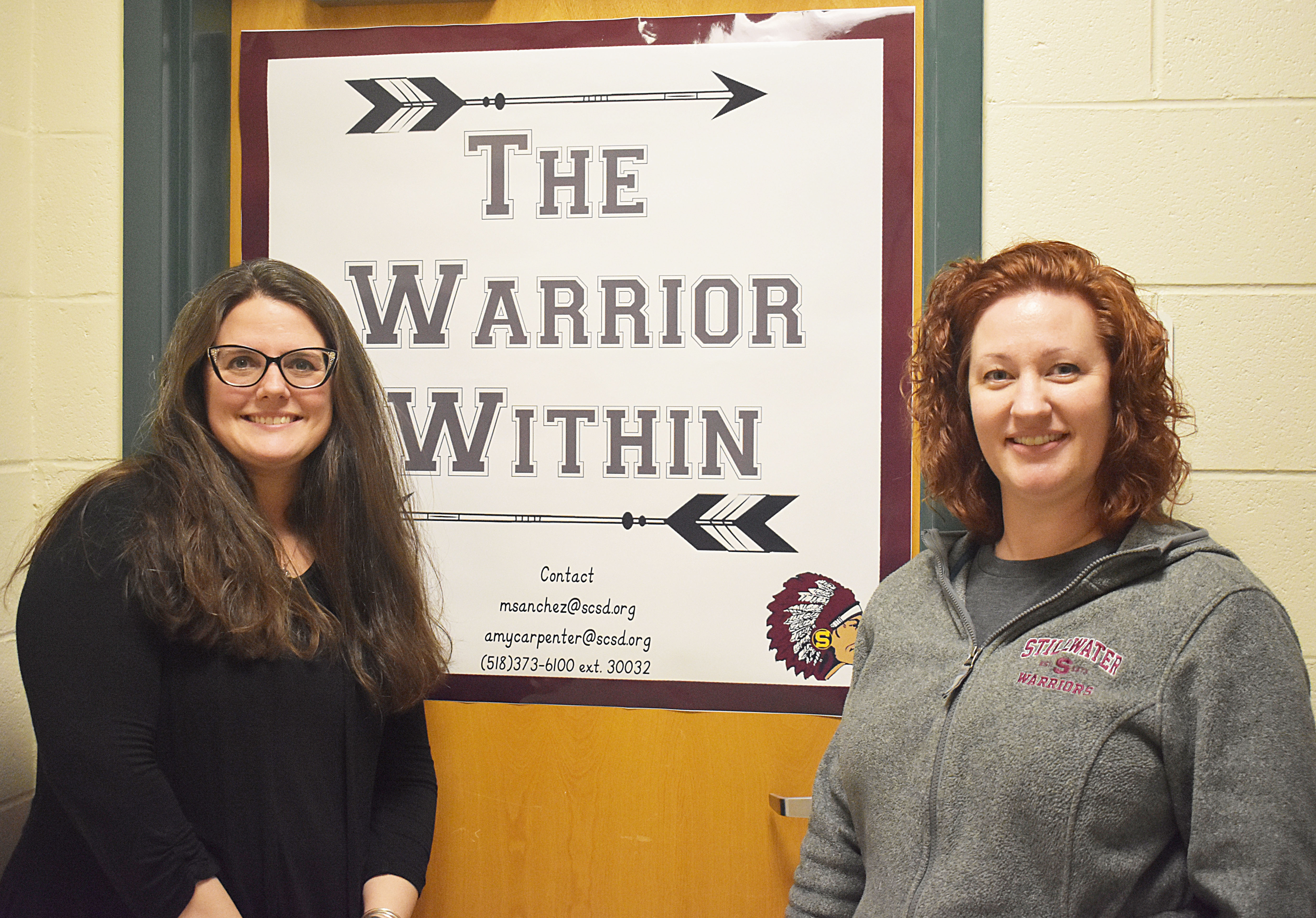 Librarian Amy Carpenter and Library Aide Megan Sanchez stand in front of Warrior Within sign