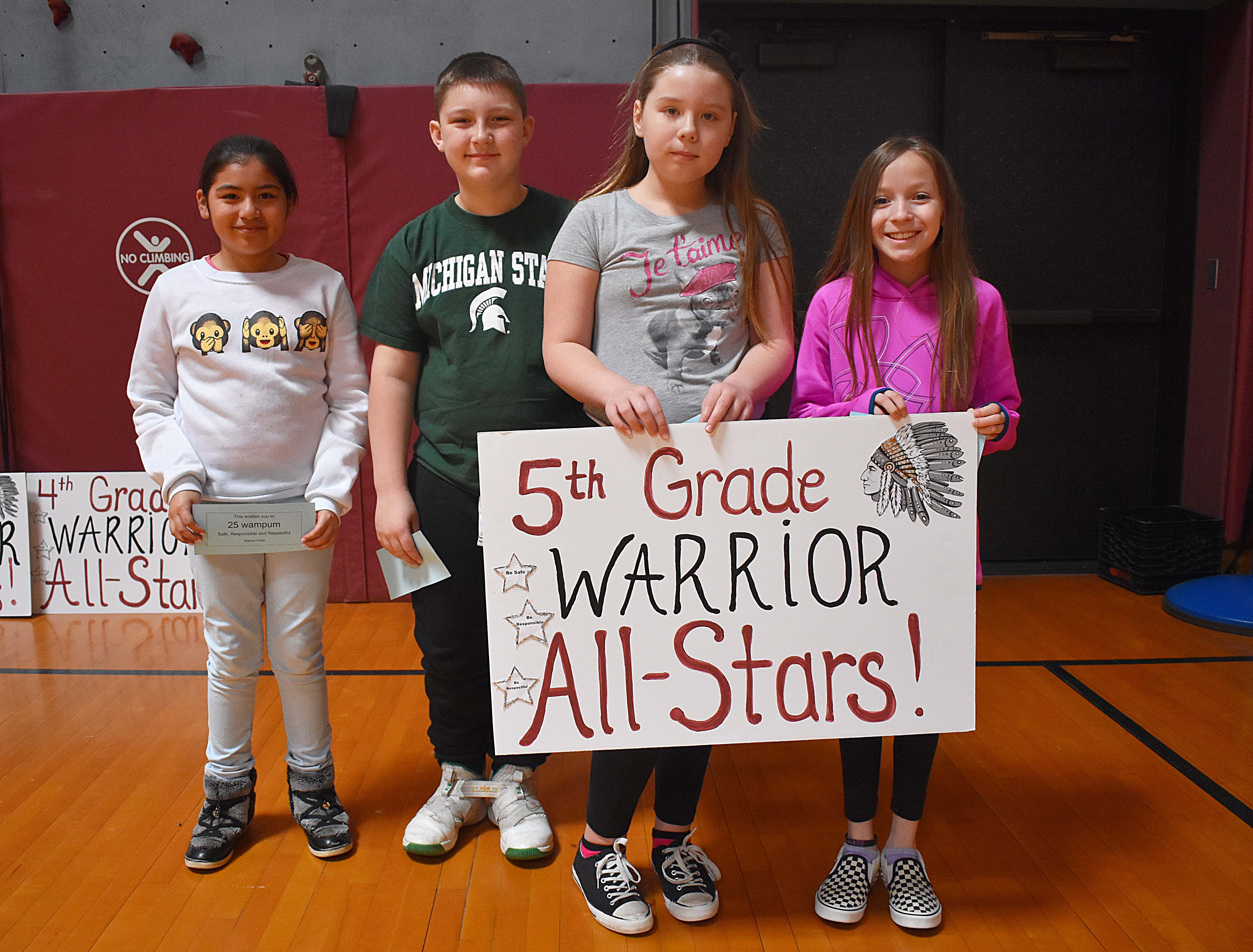 Students standing with fifth grade sign