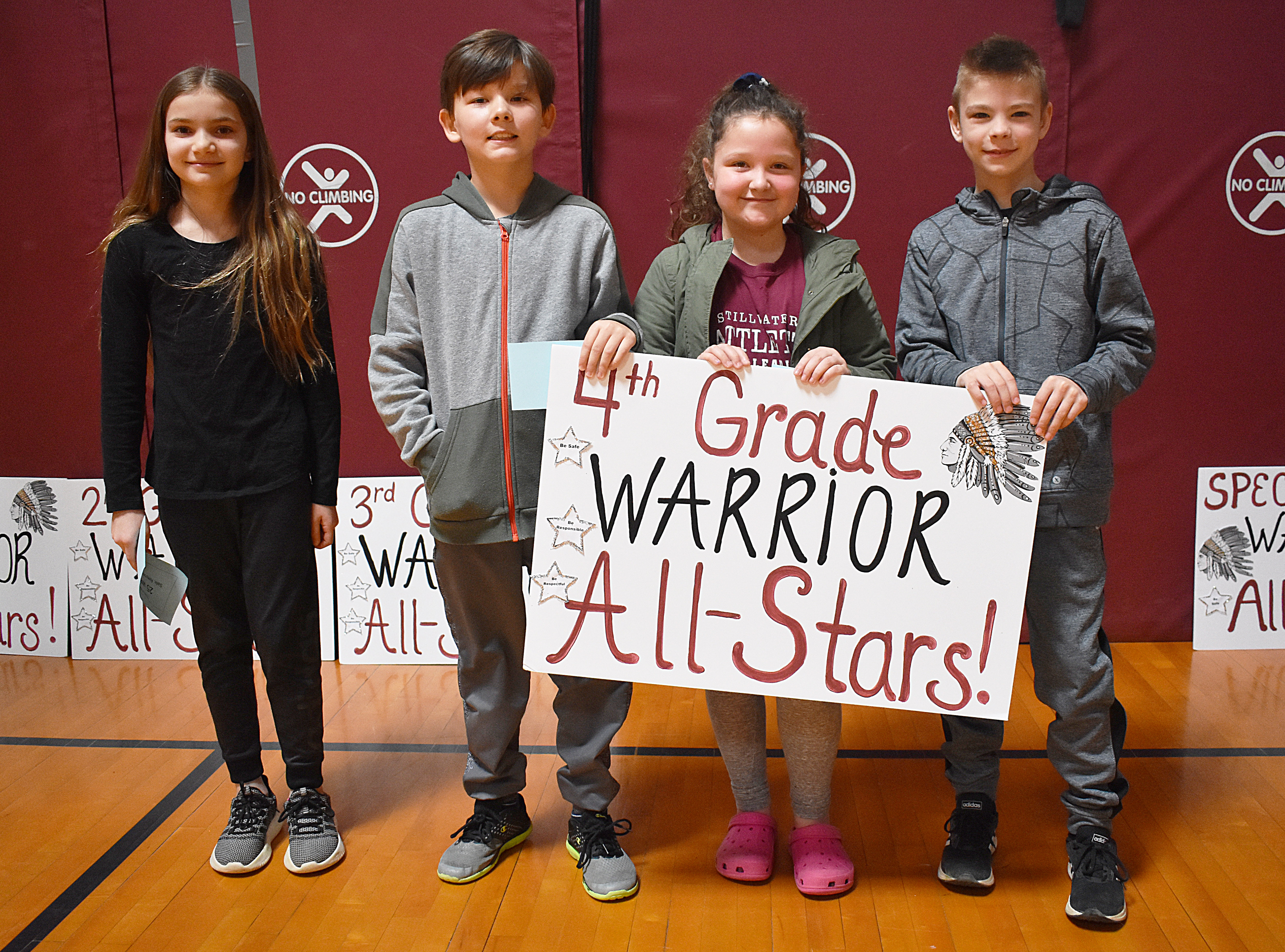 Kids standing together with fourth grade sign