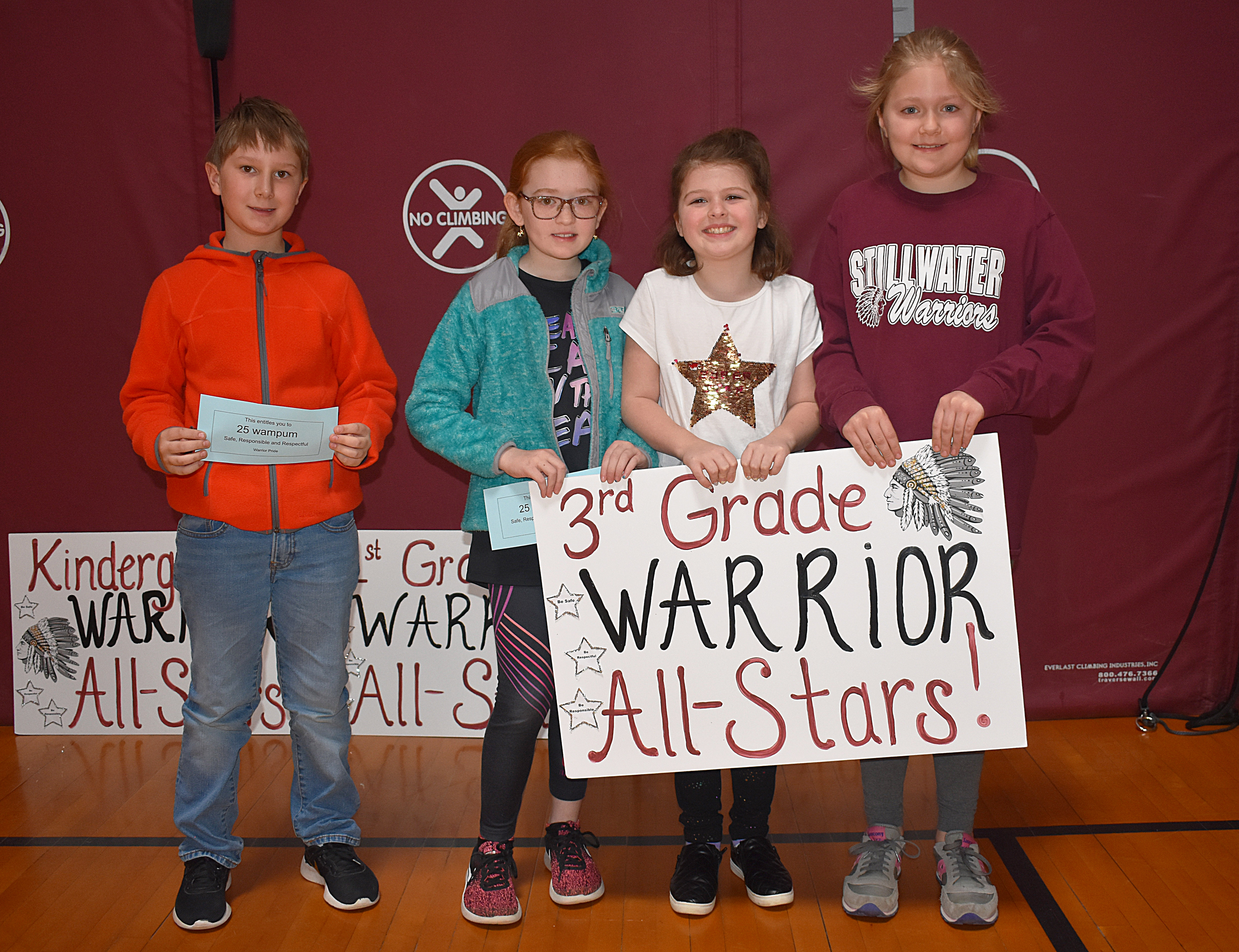 Kids standing together with third grade sign