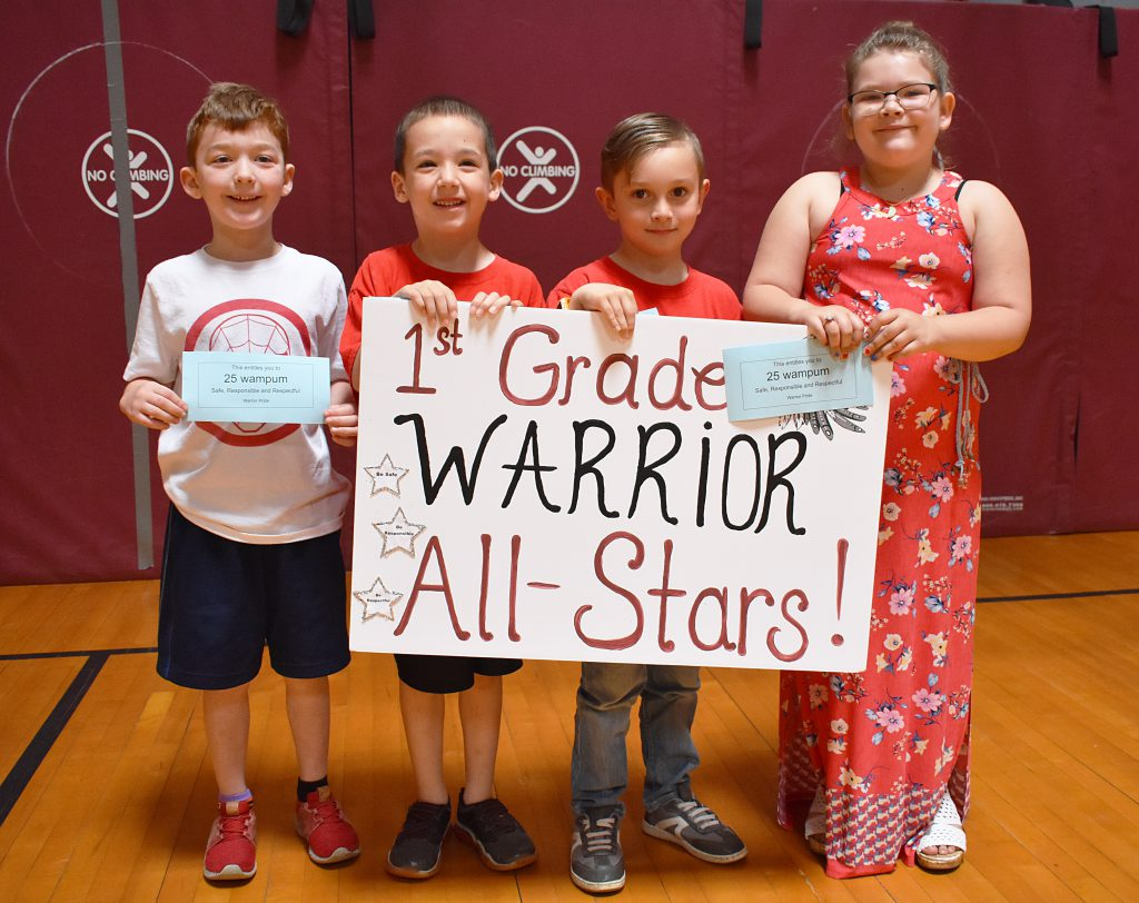 First grade students standing behind sign