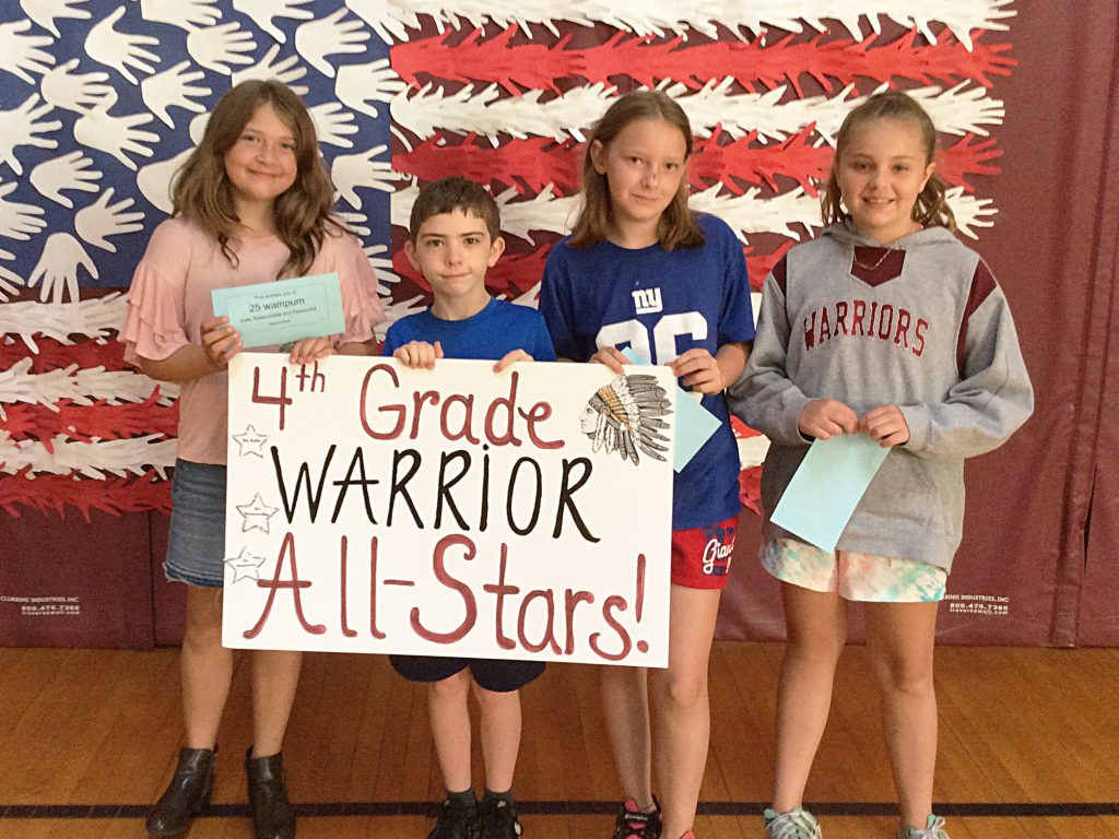 Three girls and a boy with fourth grade sign