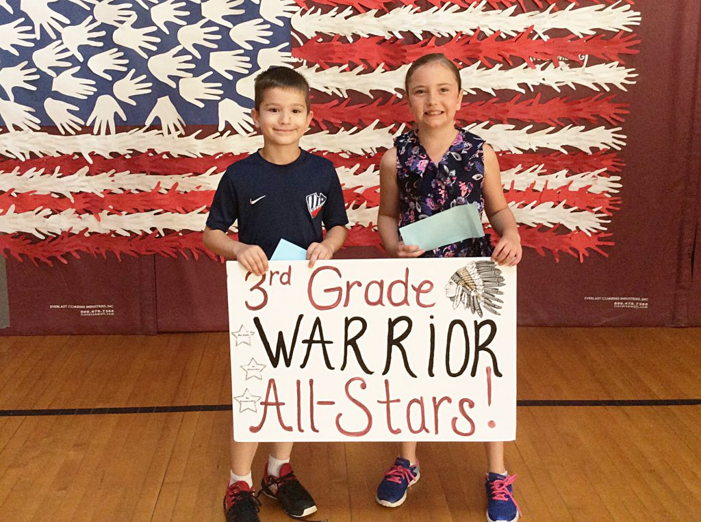A boy and a girl with third grade sign