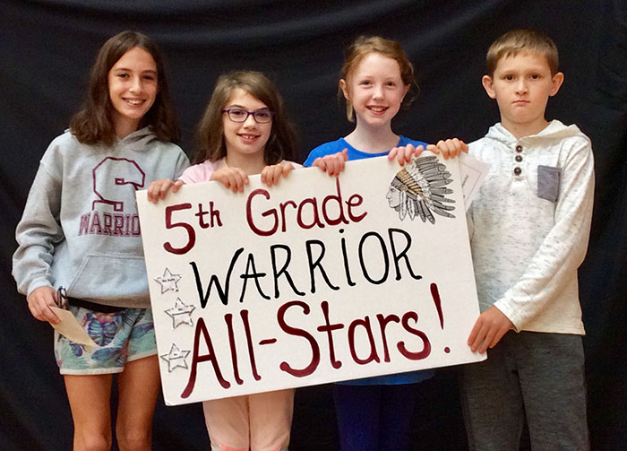 Fifth grade all stars standing with sign