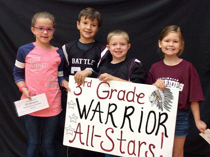 Third grade warrior all stars standing with sign