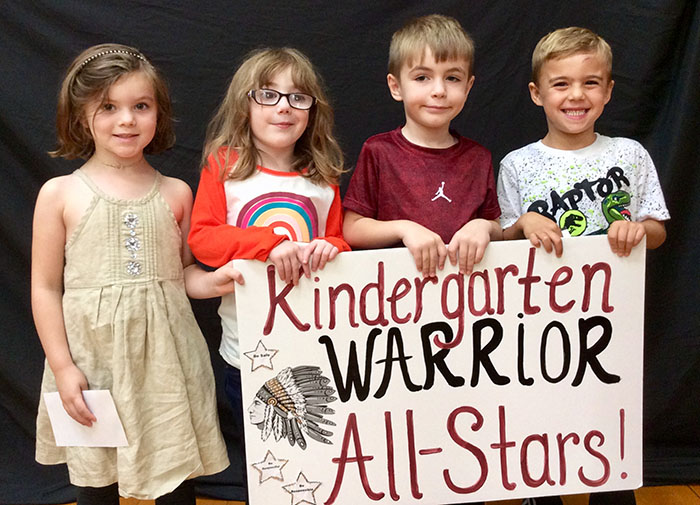 Kindergarten all stars standing with sign