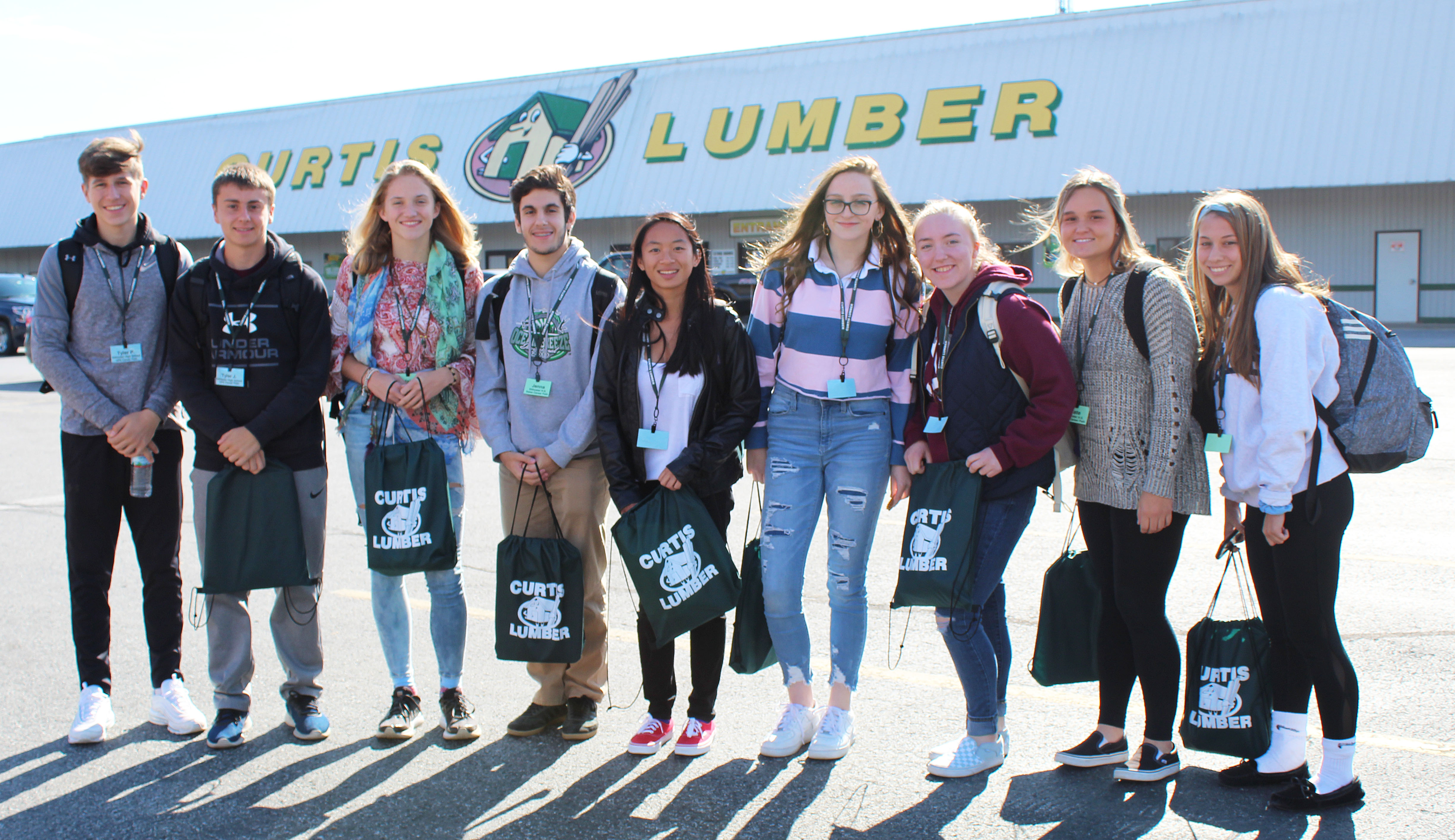 9 students lined up in front of Curtis Lumber store