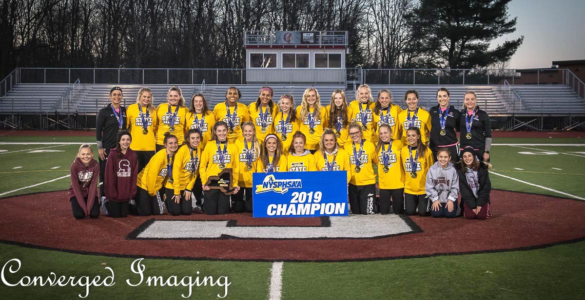 Girls team posed together with state championship banner