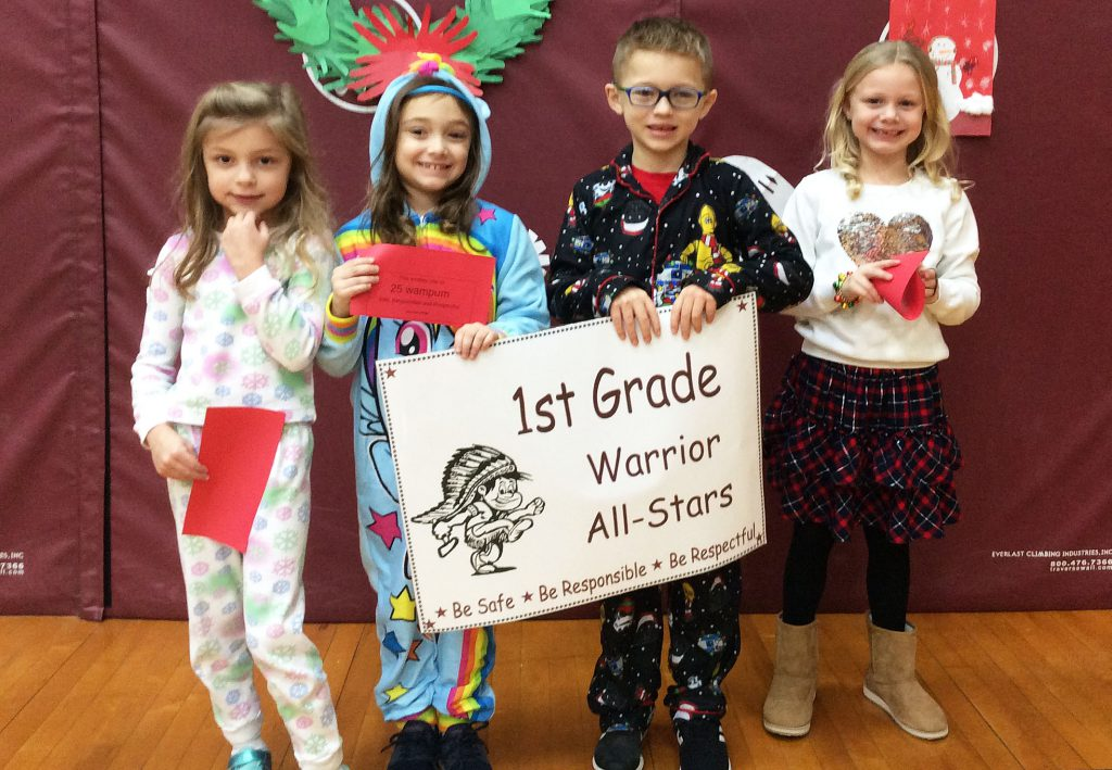 Three girls and a boy standing with first grade sign
