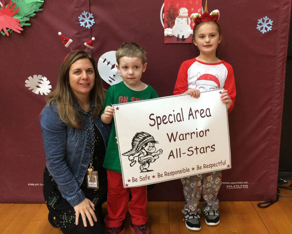 Two students and a teacher standing with specials sign