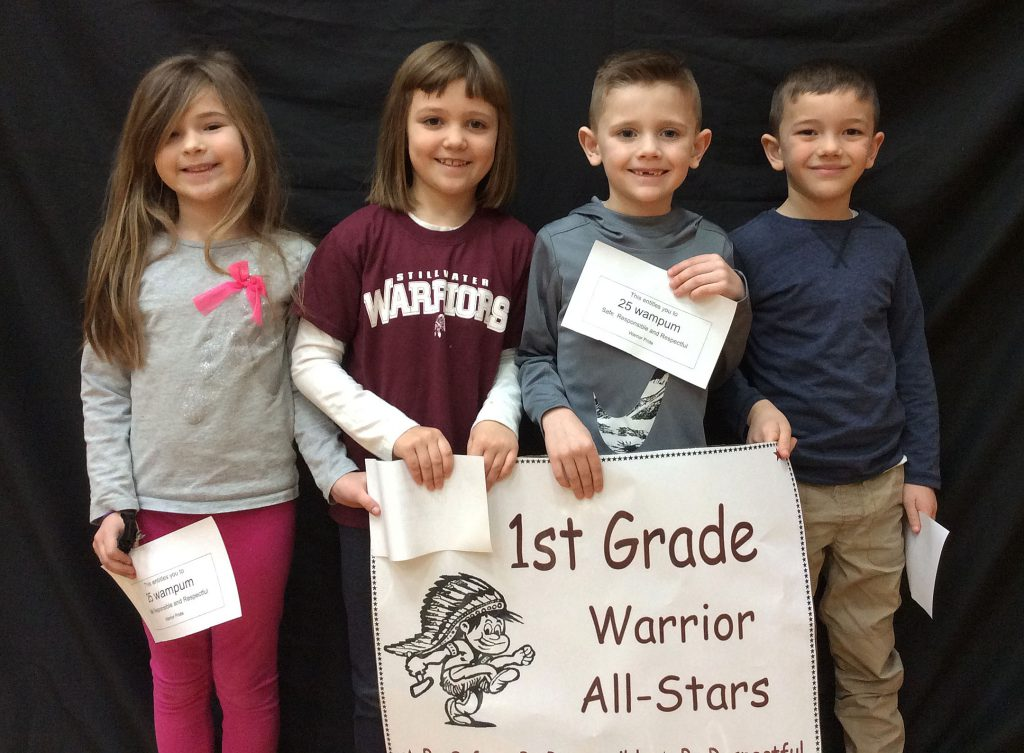 Four first grade students standing with Warrior All Star sign