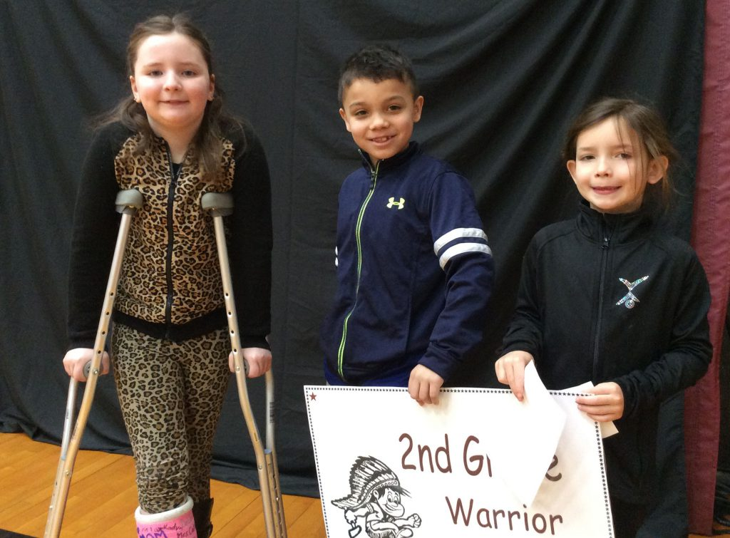 Three second grade students standing with Warrior all star sign