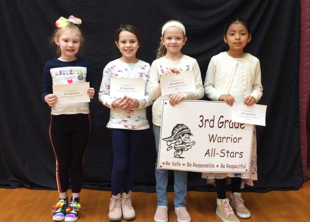 Four third grade students standing with warrior all star sign