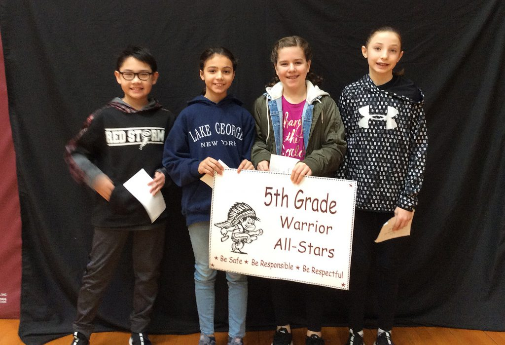 Four fifth grade students standing with fifth grade warrior all star sign