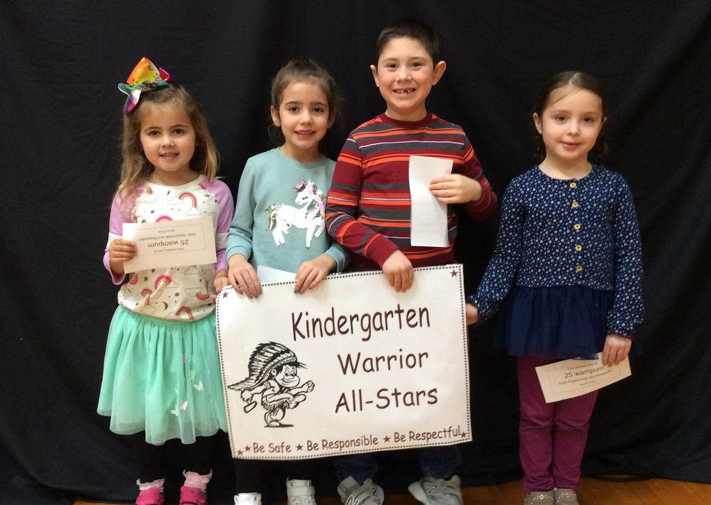 Four students standing with kindergarten warrior all-star sign