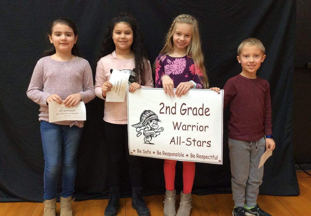 Four students standing with second grade warrior all-star sign