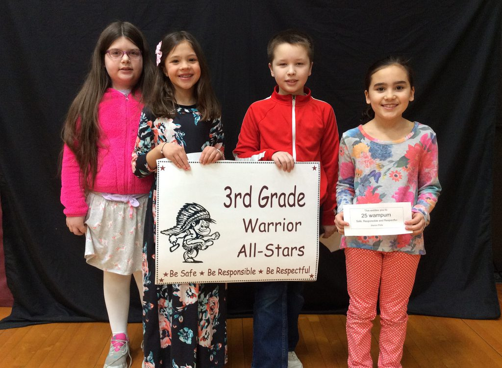 Four third grade students standing with warrior all-star sign