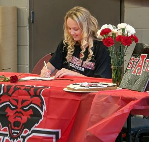 Student sitting at a table with a red table cloth signing a piece of paper