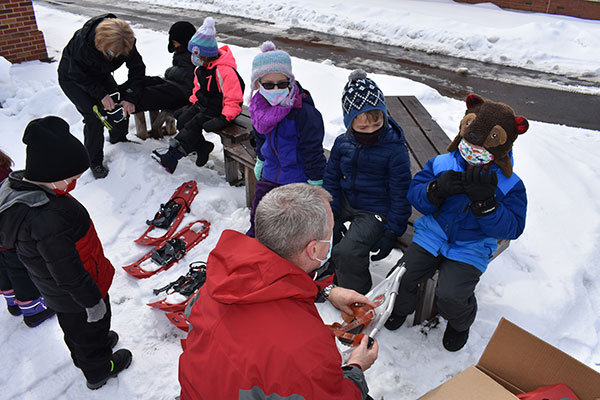 Superintendent and Assistant Principal help students put on snowshoes