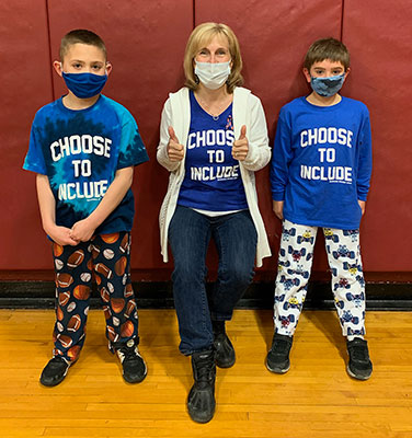 Superintendent standing with 2 students, all wearing Choose to Include shirts