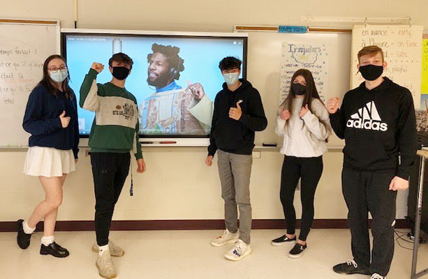 students in front of a video screen with a musician on it