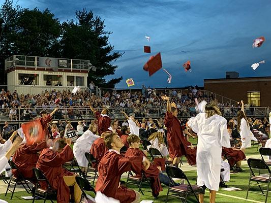 graduates toss their hats