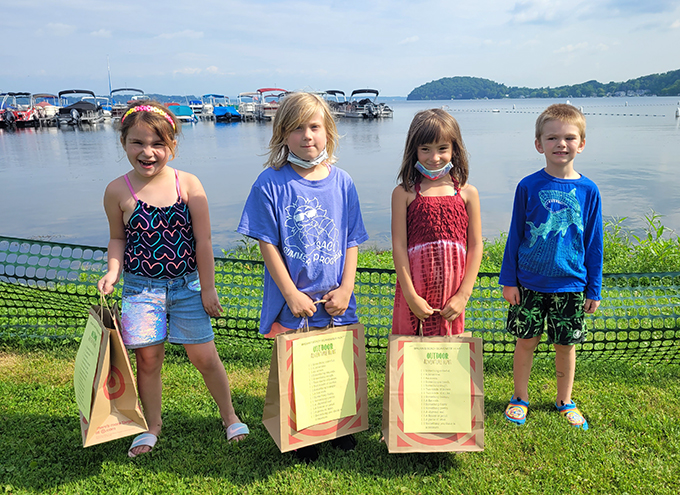 students holding bags in front of lake